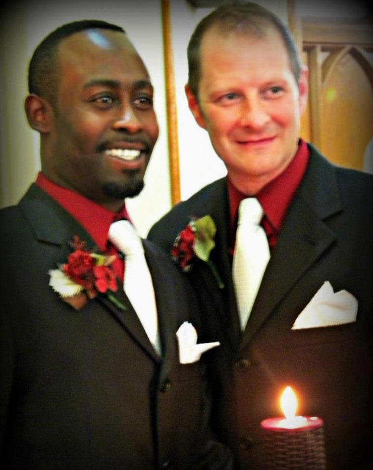 Bishop Erik Swope-Wise, right, and his husband Kelsey Swope-Wise stand before a unity candle on their wedding day on April 28, 2012. The photo was inadvertently removed from Facebook by the site after a complaint was made about the image.