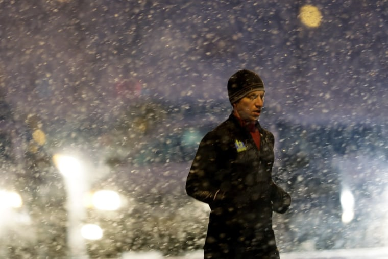 A runner passes crosses a street during a winter snow storm, Friday, in Philadelphia.
