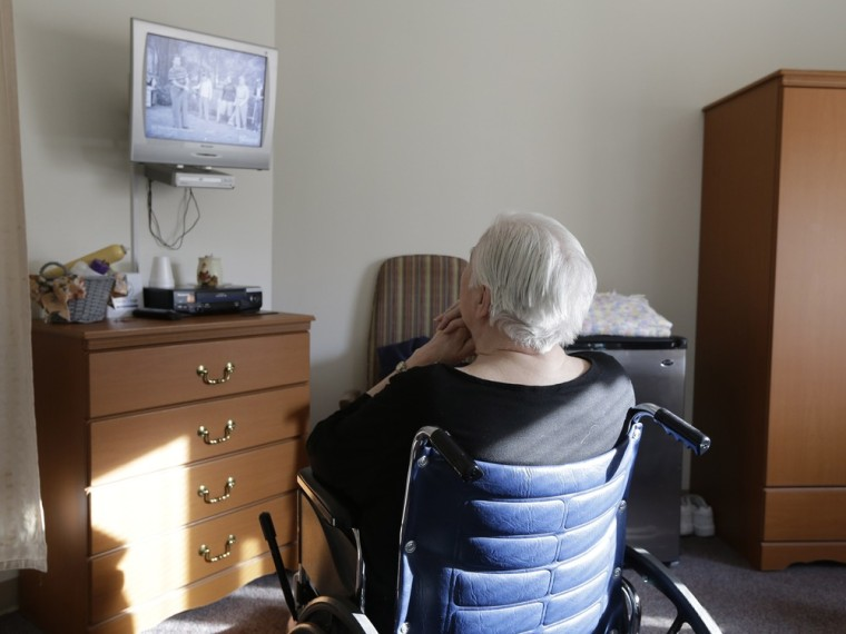An elderly woman who has suffered abuse by a relative watches