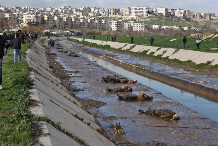 Locals gather at the banks of a small canal containg the bodies of dozens of people on Jan. 29 in Aleppo, Syria.