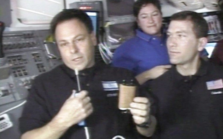 Israeli astronaut Ilan Ramon holds up a miniature Torah scroll during Columbia's final mission in 2003, as fellow astronaut Laurel Clark and mission commander Rick Husband look on.