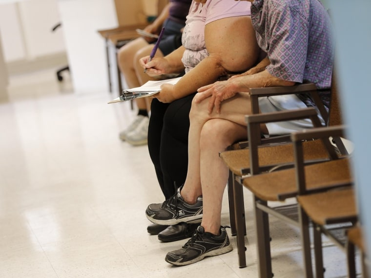 Uninsured patients fill out paperwork.