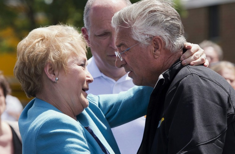 Raymond Lafontaine, who lost his son and two daughters-in-law, receives a hug from Quebec Premier Pauline Marois during her visit to Lac-Megantic, Quebec, Thursday, July 11, 2013. Marois toured the site of Canada's worst railway catastrophe in almost 150 years, after a runaway oil train killed 50 people in a fiery explosion.