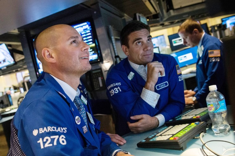 Traders work on the floor of the New York Stock Exchange at the end of the trading day Thursday. The Dow Jones Industrial Average closed at record hig...