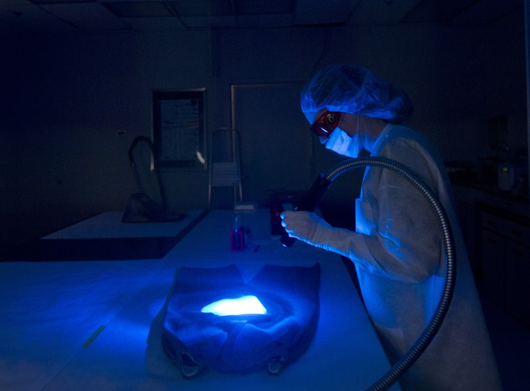 Kimberly Stoddard, a forensic scientist at the New York State Police Forensic Investigation Center in Albany, N.Y., scans a garment for biological evidence in 2012.