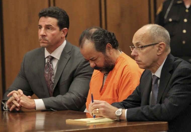 Ariel Castro sits with his head down between his attorneys Jaye Schlachet, right, and Craig Weintraub, left, during his pre-trial hearing on charges including rape, kidnapping and murder in Cleveland, Ohio on June 19, 2013.