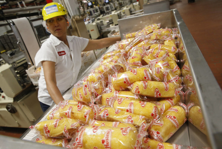 """A worker boxes up \""""Twinkies\"""" at a plant in Schiller Park, Illinois, July 15, 2013. The Twinkie returned to production after the Hostess's snack cake b..."""