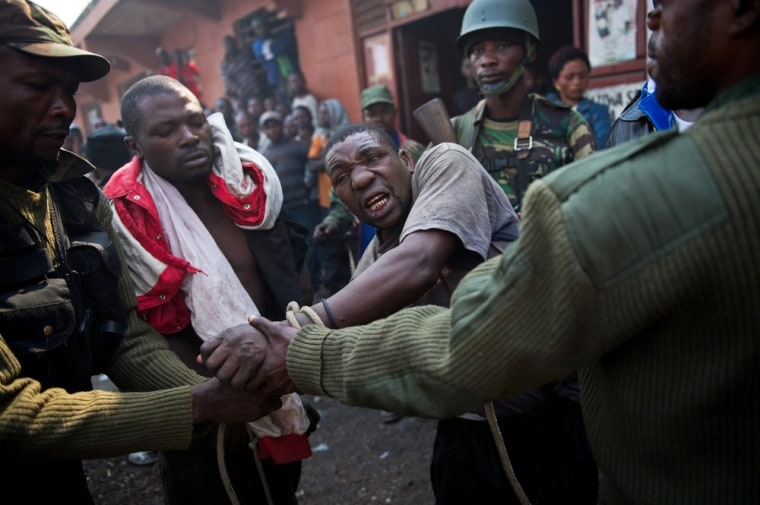 A man accused by the Congolese Army of being a spy for rebels of the M23 movement is tied up and taken away on July 16, 2013, in Munigi, on the outskirts of Goma.