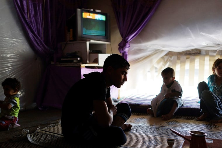A family from the city of Homs watches television in their tent inside a camp for Syrians who have fled the fighting in their country on June 28, 2013 in Baalbek, Lebanon.