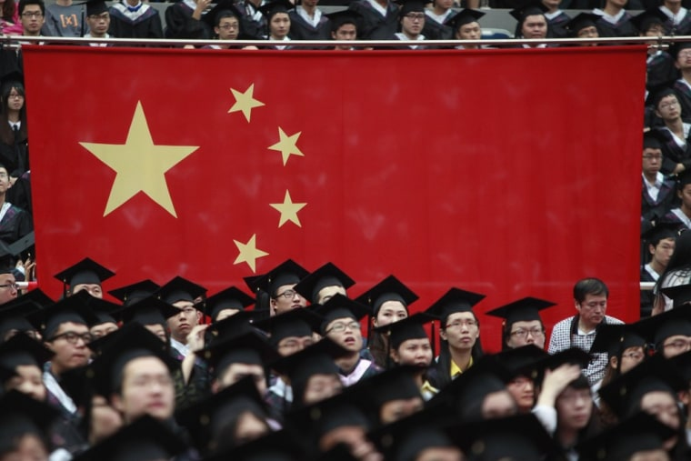 Graduates set next to the Chinese flag during a graduation ceremony at Fudan University in Shanghai June 28, 2013.