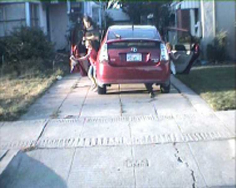 An image taken by a license plate reader on a San Leandro, Calif., police car shows Mike Katz-Lacabe and his daughters getting out of their Toyota Prius in their driveway. The image is one of 112 that Katz-Lacabe received in a 2010 public records request for license plate data on his vehicles collected by police.