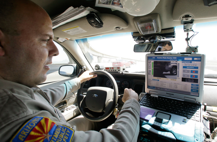 Arizona Department of Public Safety officer David Callister watches his dashboard computer as it reads passing car license plates from an infrared camera mounted on the front bumper of his police cruiser in 2007 in Phoenix. The cameras can read thousands of license plates during a routine shift, far more than an officer could do by hand.