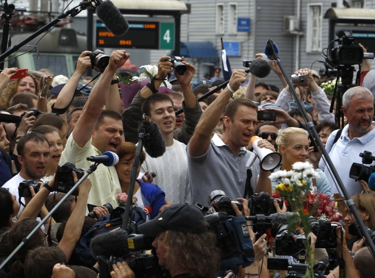 Russian protest leader Alexei Navalny and his co-defendant Pyotr Ofitserov surrounded by supporters and journalists, gesture after arriving from Kirov at a railway station in Moscow, July 20, 2013.
