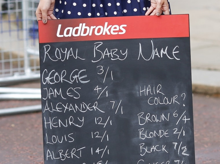A woman holds a Ladbrokes board listing possible baby names to bet on.
