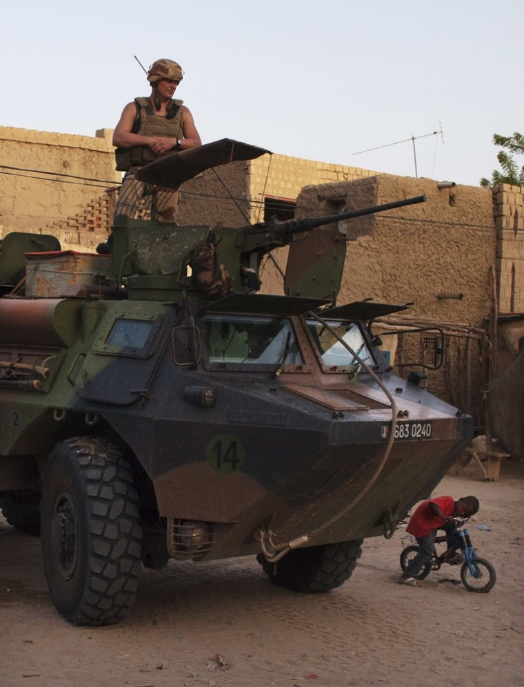 A boy on a bicycle peeks out from underneath a French soldier on patrol in an armored personnel carrier in Timbuktu, July 25.