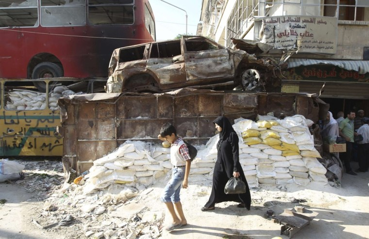 People walk past a makeshift barricade at the Garage al-Hajz crossing, a passageway separating the rebel-controlled Bustan al-Qaser district from the regime-controlled Al-Masharqa neighborhood, in Aleppo on July 18, 2013.