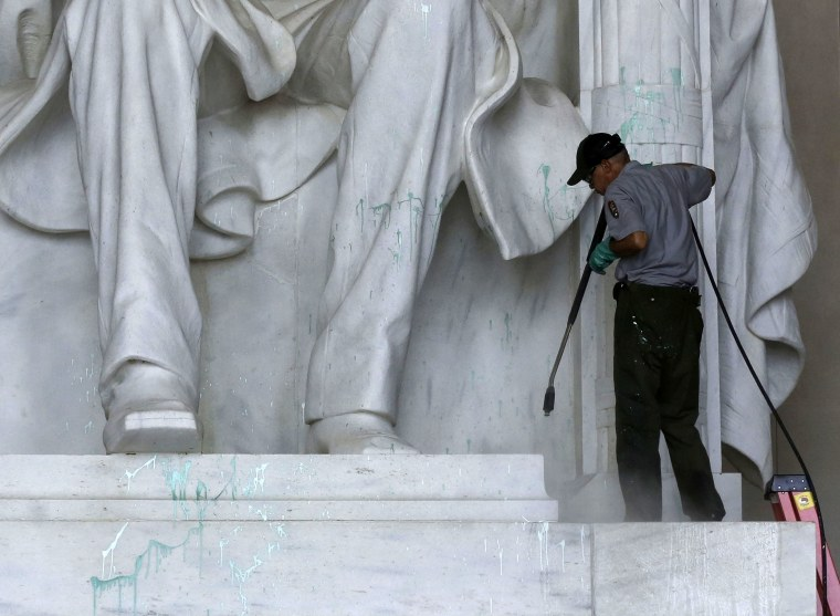 A National Park Service employee uses a pressure hose to clean green paint from the Lincoln Memorial in Washington on Friday.