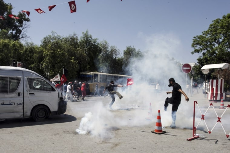 Tunisian opposition politician Mohammed Brahmi's supporters run in the tear gas during clashes with police after the funerals in Tunis, Saturday July, 27, 2013.