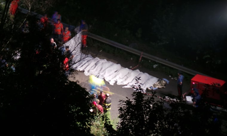 Rescuers line up the bodies of victims of a bus crash on July 28, 2013 on the road between Monteforte Irpino and Baiano, southern Italy. At least thirty people died and dozens were injured in southern Italy on Sunday when a coach came off a flyover and plunged 30 metres (98 feet) down a slope, according to Italian media.