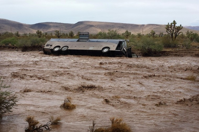 A Las Vegas-bound tour bus lies on its side near Dolan Springs, Ariz., Sunday, after it was caught by floodwaters in a desert wash.