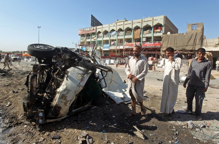 Iraqis inspect the site of a car bomb explosion in the impoverished district of Sadr City in Baghdad. It was one of just a dozen deadly explosions in Iraq Monday.