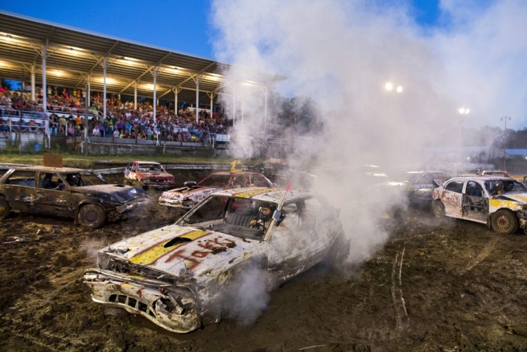 Contestants in a demolition derby kick up mud and smoke at the Hardin County Fair in Eldora on July 14.