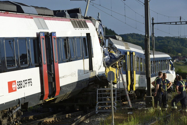 Rescue workers inspects the scene of a train collision in Granges-pres-Marnand in western Switzerland on July 29.