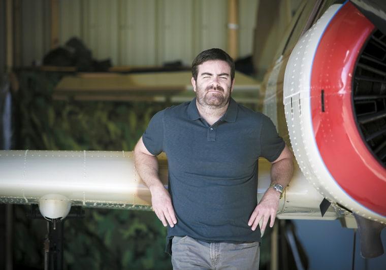 Former Navy SEAL Brandon Webb poses with his Yak 52 airplane in a hangar in El Cajon, Calif.