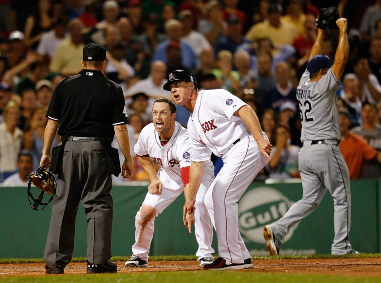 Daniel Nava #29 and Brian Butterfield #13 of the Boston Red Sox plead their case after umpire Jerry Meals called Nava out at the plate against the Tampa Bay Rays in the 8th inning at Fenway Park on July 29, in Boston, Mass.  Nava's run would have tied the game.