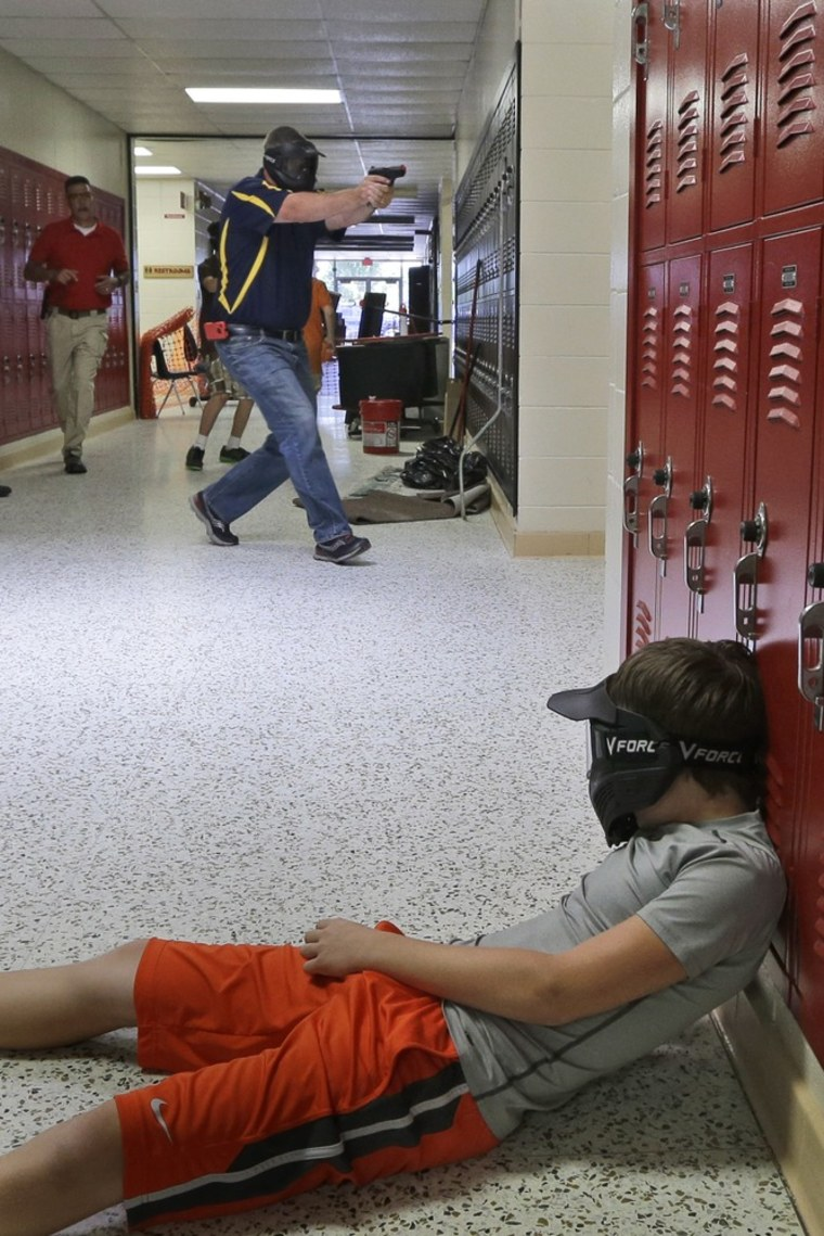 In this photo taken July 11, a Clarksville schools faculty member, wearing a protective mask, rear center, carries a practice handgun toward a classroom in the city's high school in Clarksville, Ark.