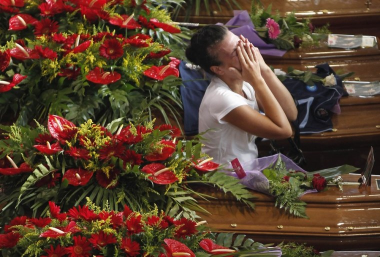 A woman cries next to the coffins of victims of a coach crash during their funeral service at the Monteruscello Palasport near Pozzuoli, Italy, on July 30, 2013.