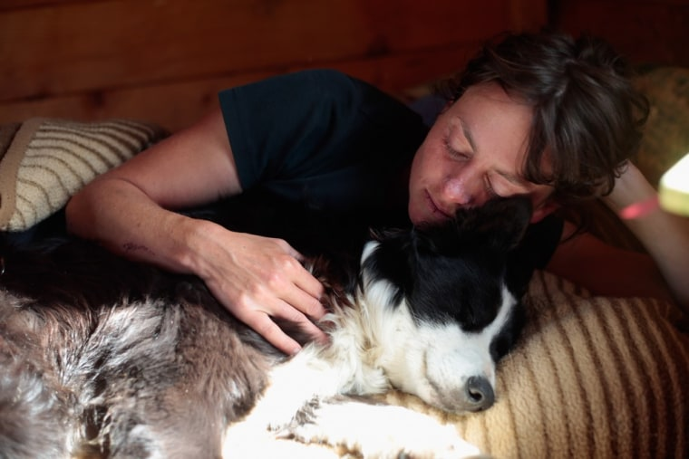 Katharina Brueggebors relaxes inside her hut with sheepdog Nelly.