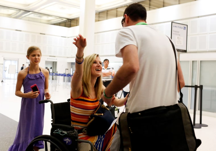 Boston bombing survivor Rebekah Gregory, center, greets her boyfriend Pete DiMartino after he arrives from Rochester, N.Y., on July 24, 2013, in Houston at Bush Intercontinental Airport. Gregory's mother Tina Gregory, left, and sister Allie Gregory, 11, stand behind Rebekah.