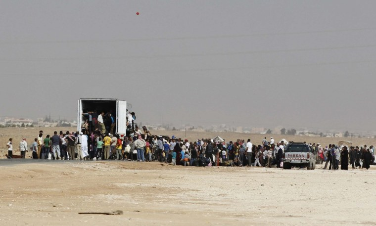 Syrians refugees try to enter a truck which will transport them back to their homeland.