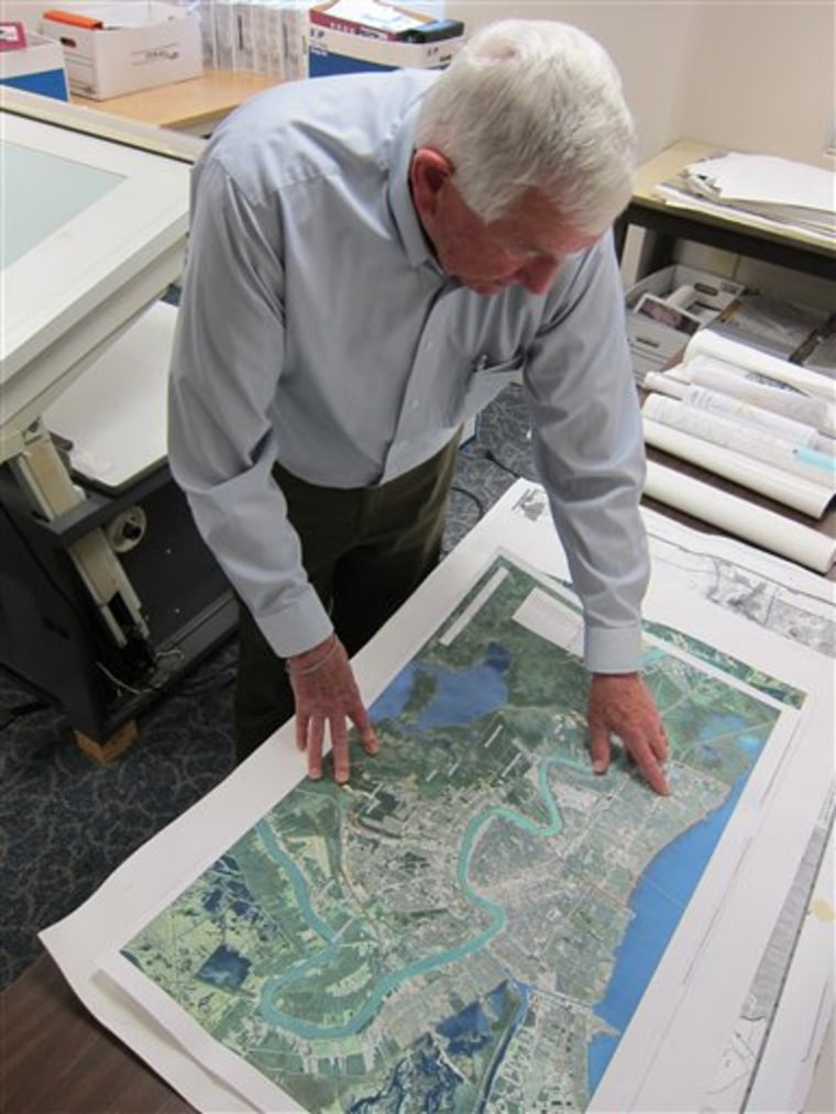This photo taken May 3, 2013 shows John Sayles, 79, a planner at Stanley Consultants, reviewing a map from a New Orleans project he worked on, at the ...