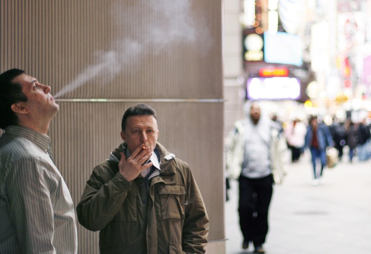 Smokers stand outside of an office building in New York City in 2009. A new study calculates that smokers cost their employers $6,000 more a year than nonsmokers.