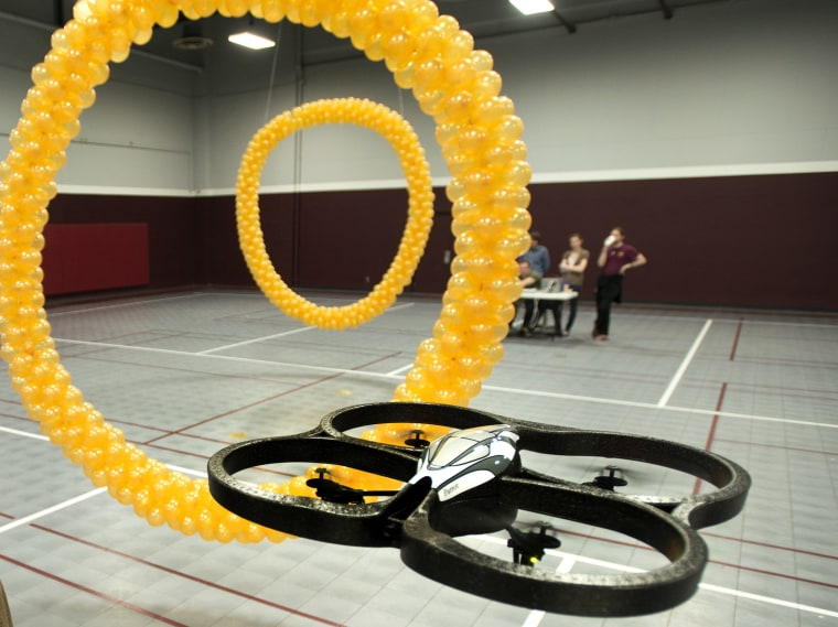 Guided by brainwaves, a Parrot quadracopter flew through two orange hoops.