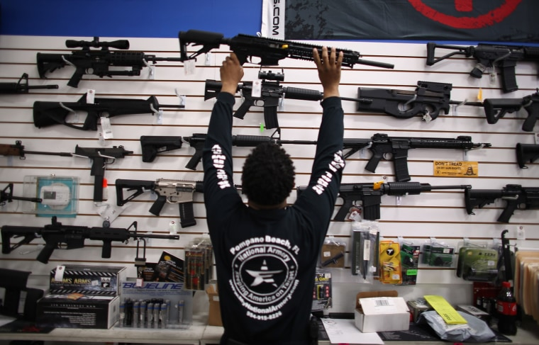 Mike Acevedo puts a weapon on display at the National Armory gun store on April 11, 2013 in Pompano Beach, Florida. The Institute of Medicine laid out a path Wednesday for research on firearms violence.