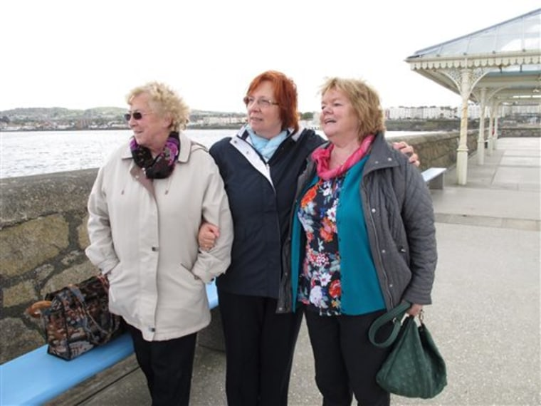 In this May 13, 2013 photo, Marie Theresa Gill, center, poses with her friends Kathleen Greenhough, right, and Mary Murray at the pier in Dun Laoghair...