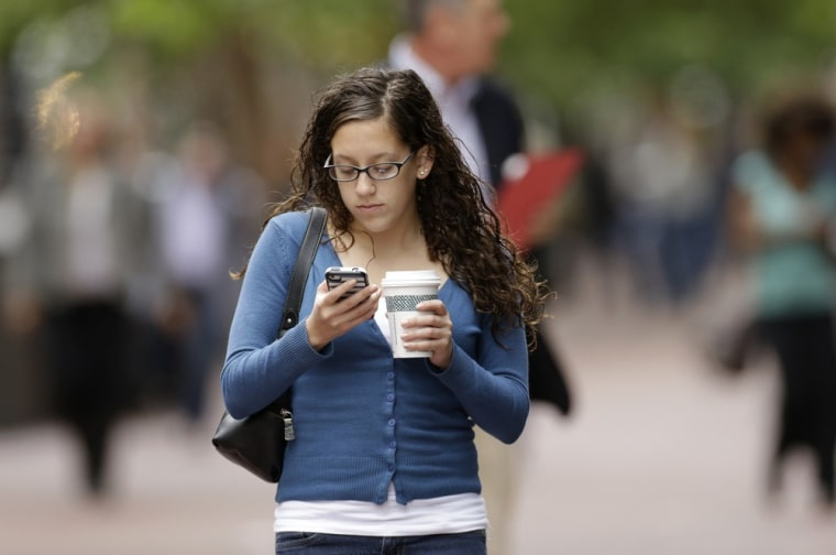 A woman uses a cellphone in downtown San Francisco Wednesday, June 5, 2013.  San Francisco's district attorney and New York's attorney general say the...
