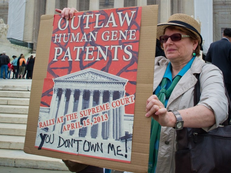 A woman holds a banner demanding a ban over human genes patents during a protest outside the Supreme Court in Washington on April 15.