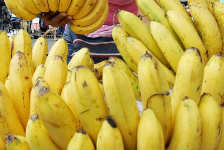 A fruit vendor arranges bananas for sale Saturday, Sept. 6, 2008, in a public market in Manila, Philippines.