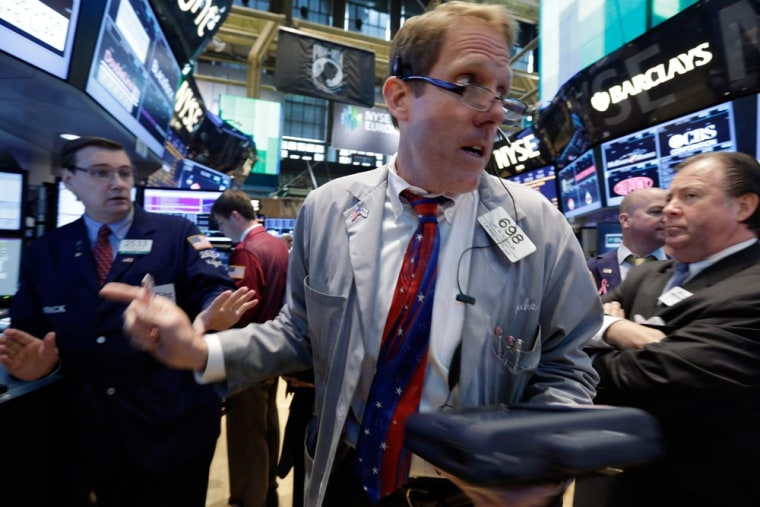 Trader Luke Scanlon, center, moves from post to post as he works on the floor of the New York Stock Exchange Tuesday, June 11, 2013.