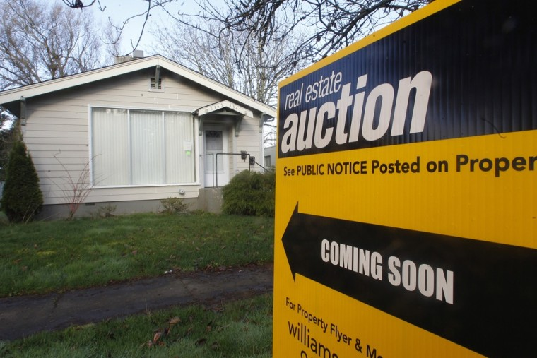 This Feb. 23, 2012, photo shows a auction sign in front of a home, in Salem, Ore.