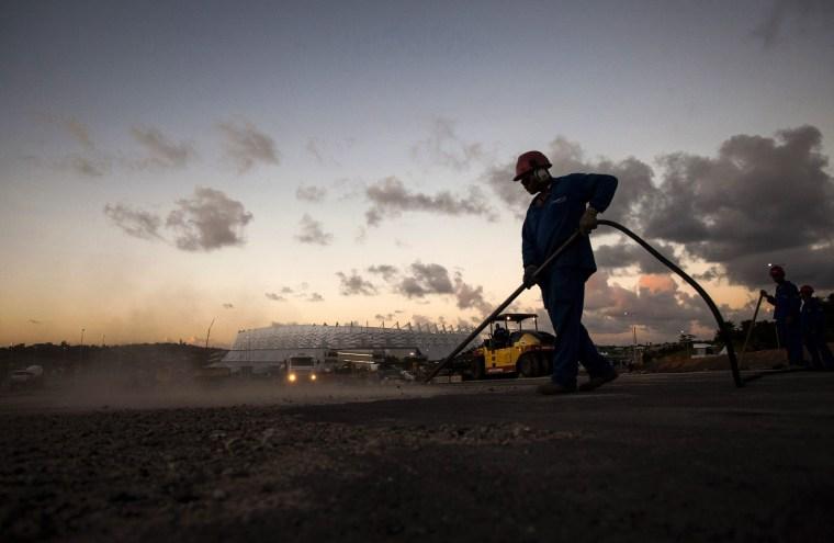 A man works near the Arena Pernambuco stadium in Sao Lourenco da Mata, a suburb of Recife