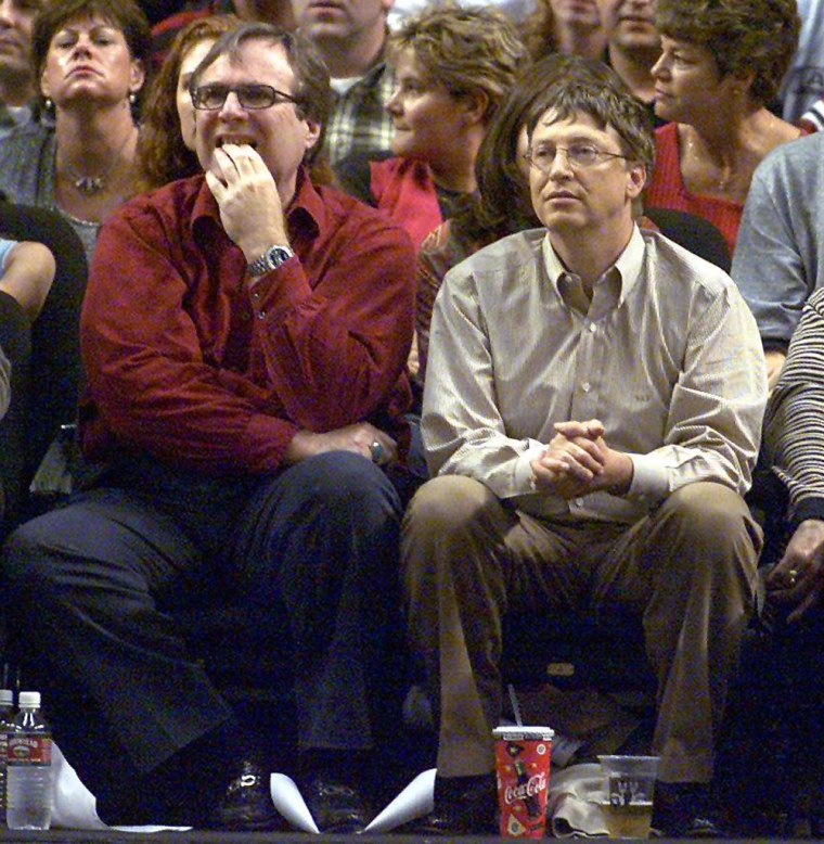 Microsoft co-founders Bill Gates (C) and Paul Allen (L) watches the third game of the Western Conference Finals between the Los Angeles Lakers and the...