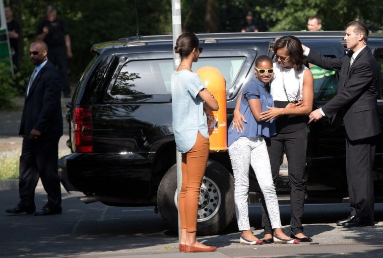 Michelle Obama hugs her daughter Sasha as they arrive to visit the Holocaust Memorial.
