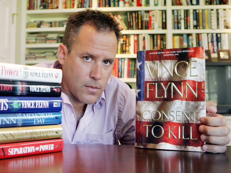 """Best-selling author Vince Flynn poses with the dust jacket of his new book, \""""Consent to Kill,\"""" and copies of his six other books in his home in Edina,..."""
