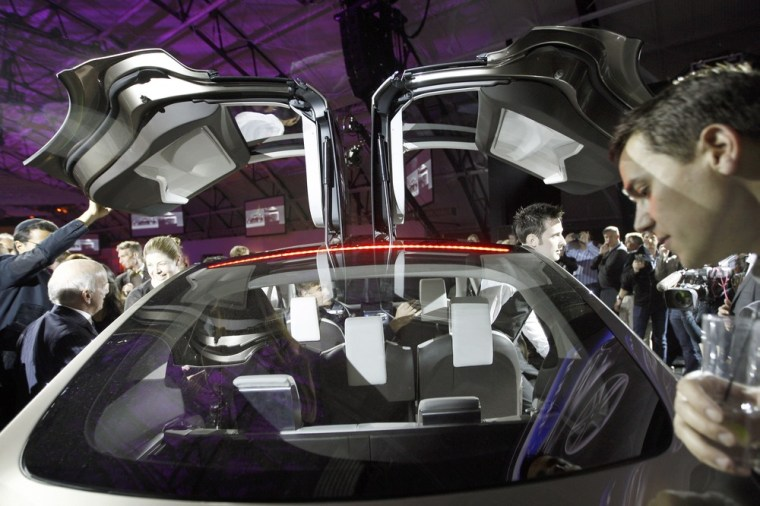 People look at the Tesla Motors Model X electric vehicle at its unveiling at the Tesla Design Studio in Hawthorne, Calif. in February 2012. The compan...