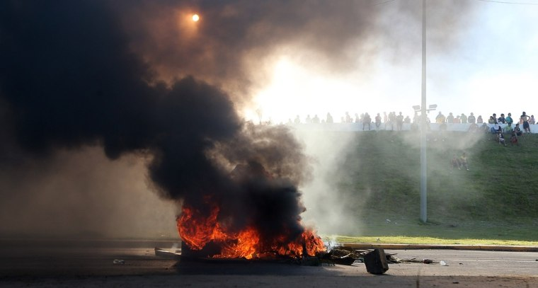 Protestors line a highway barrier in front of a burning barricade of tires near the Castelao stadium in Fortaleza, Brazil, Wednesday, June 19, 2013. Protesters cut off the main access road to the stadium where Brazil goes up against Mexico in the Confederations Cup soccer tournament. Beginning as protests against bus fare hikes, demonstrations have quickly ballooned to include broad middle-class outrage over the failure of governments to provide basic services and ensure public safety.